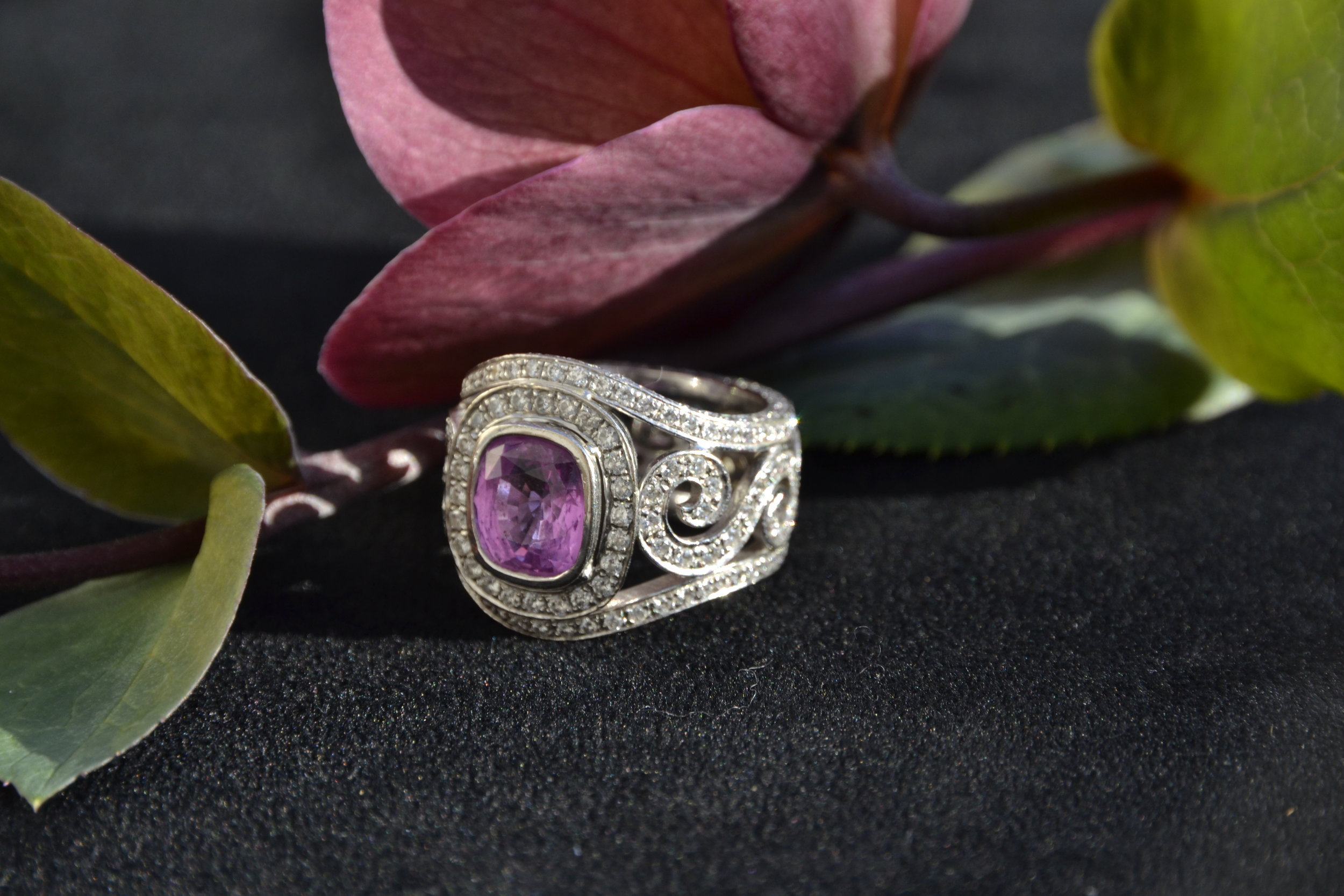 Cushion cut pink sapphire set with diamonds