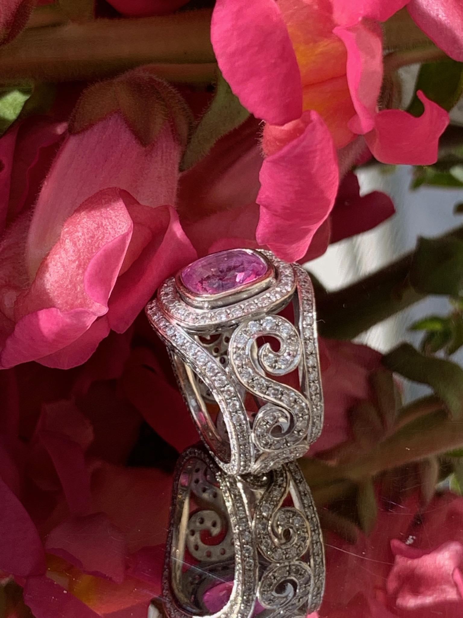 Cushion cut pink sapphire set with lots of diamonds